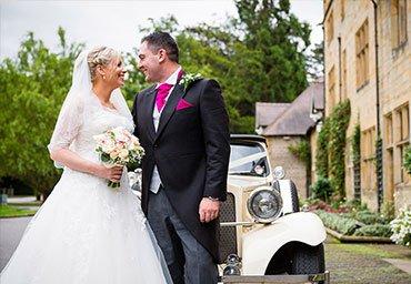 Married portrait beside the wedding car.
