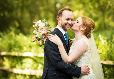 Bride kissing husband wedding photo